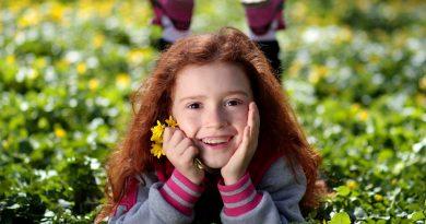 Kind auf Wiese mit Blume