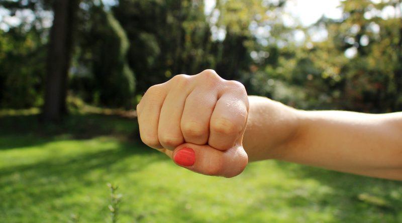 Faust mit rotem Fingernagel