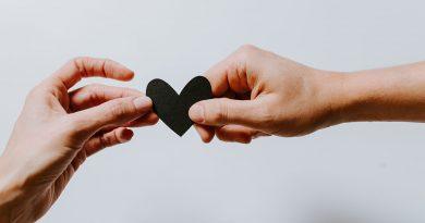 zwei Hände halten ein schwarzes Herz