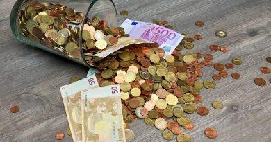 Euromünzen und Scheine in einem Glas