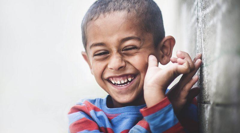 lachender Junge im rot-blauen Pullover