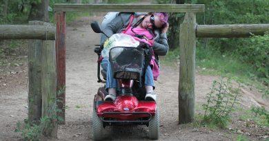Frau im Rollstuhl an einer Barriere