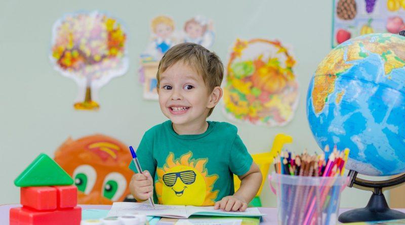 fröhliches Schulkind mit Buntstiften und Globus