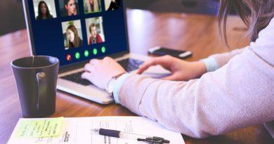 Mensch verfolgt Videokonferenz am, Schreibtsich mit Laptop, Teetasse und Schreibblock