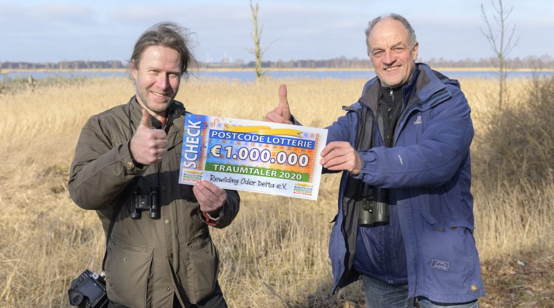 Zwei Personen halten den Spendenscheck der Postcode Lotterie