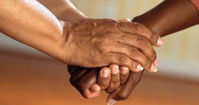 zwei Menschen halten sich an den Händen