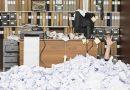 Mensch im Büro ertrinkt in Papier
