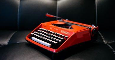 rote Schreibmaschine auf schwarzer Couch
