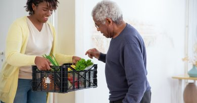 eine junge Frau hilft einem alten Mann beim Einkaufen
